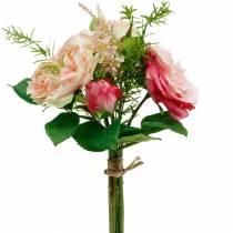 Bukett med kunstige roser i en haug med rosa bukett av silkeblomster